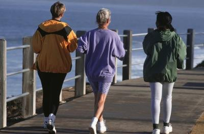 Three women take a morning jog on a pier.