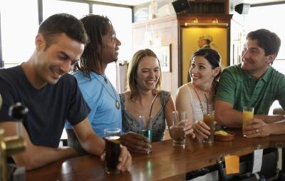 Group of friends drinking beer together in bar.