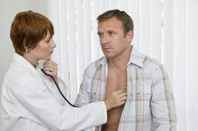 A man has his heart rate and breathing checked by a doctor.