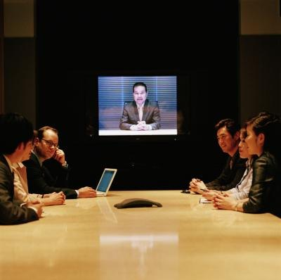 Employees meet in the conference room for a webinar.