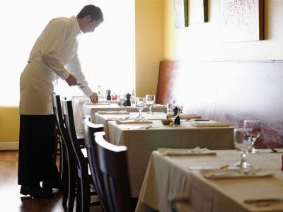 A waiter sets up a table by the window.