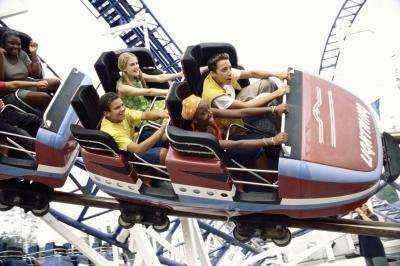 Teenage boys and girls on roller coaster ride