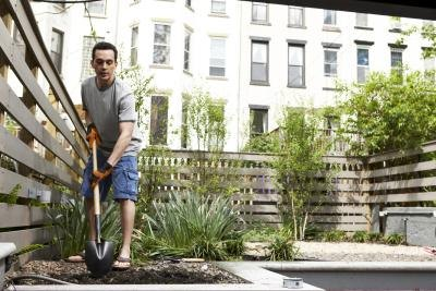 A man digs a hole to plant a tree on a rooftop urban garden.