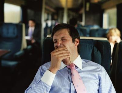 A buisnessman yawns during his train commute.