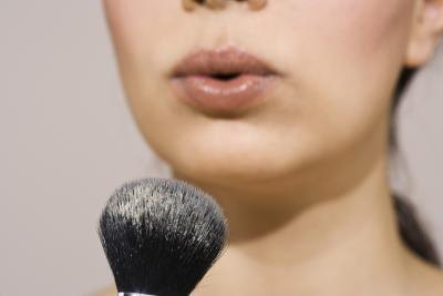 woman blowing on mineral brush