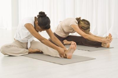 Two women practice yoga poses.