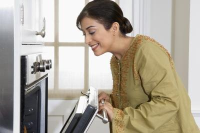 Woman opening conventional oven.