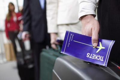 Man holding an airline ticket booklet.