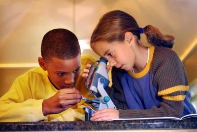 Young boy and girl looking through a microscope.