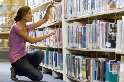 Woman looking for book in library.