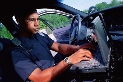 An officer works on a computer in a vehicle.