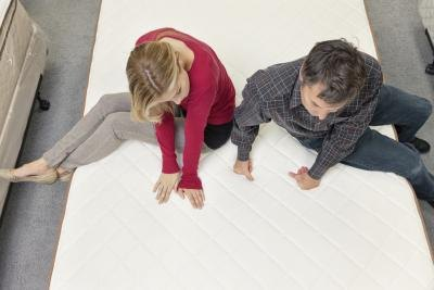 Couple testing new mattress at store