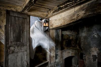 Ghost holding a lantern inside of haunted house
