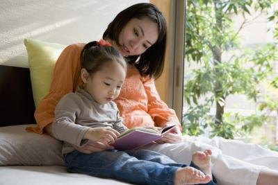 Mother reading with child in bed