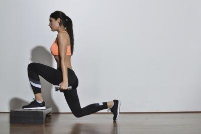 A woman doing weighted lunges.