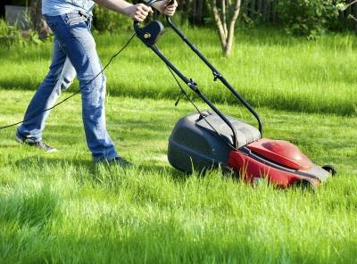 Man with electric lawn mower