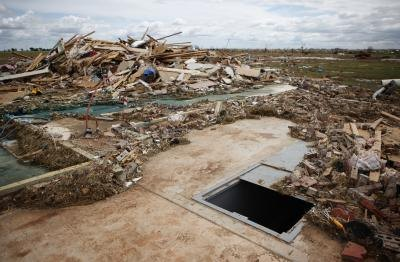 A storm shelter among tornado damage in Piedmont, OK