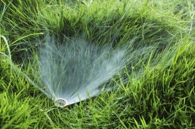 Close-up of sprinkler in grass field