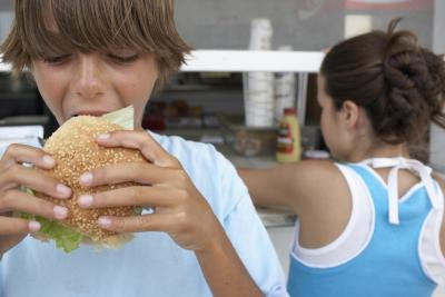 A boy eats a hamburger in front of a take-out stand.