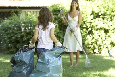 A girl drags two full garbage bags across the lawn.