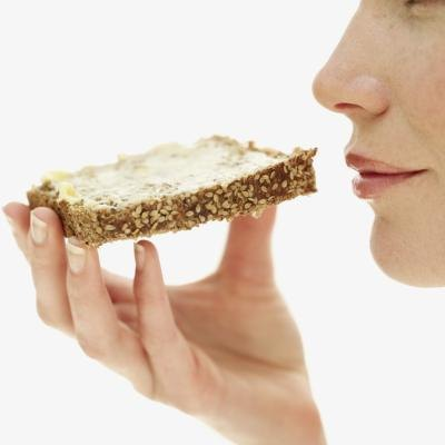 A woman eats a slice of whole grain bread.