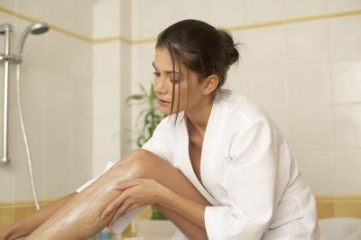 woman applying antifungal cream to leg