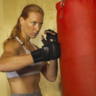 Grappling gloves and heavy bags are used in kickboxing training.