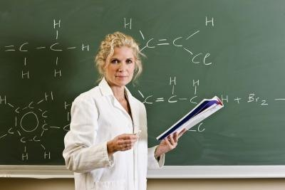 Female teacher holding book standing in front of blackboard.