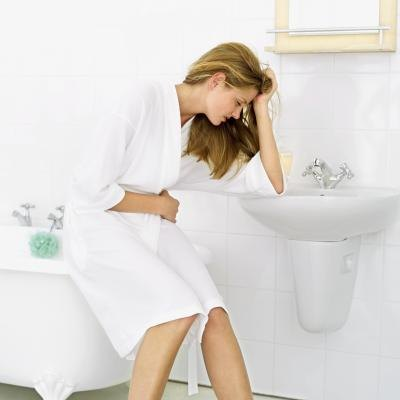 A woman huntches over a bathroom sink in pain.