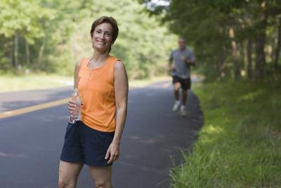 Woman going on exercise walk on side of the road.