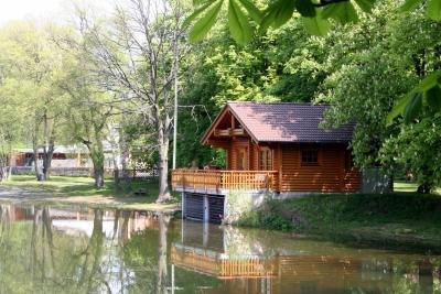 A quaint wooden cottage on a canal in the woods.