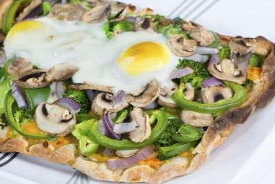 Vegetarian pizza on flat bread with two sunny side-up eggs
