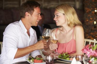 Couple toasting with white wine at restaurant