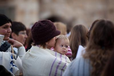 Woman wearing a shawl holds her baby at the Wailing Wall