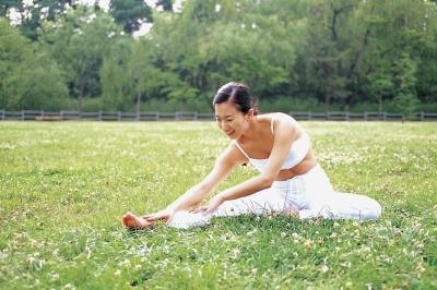 A woman stretches in a park.