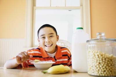 A young boy eating a bowl of Kix cereal.