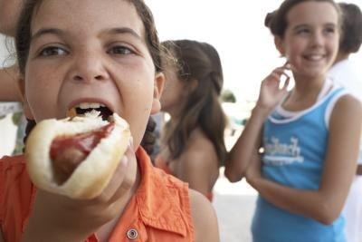 A girl takes a bite of a hot dog with ketchup.