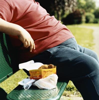 An overweight man sits on a bench.