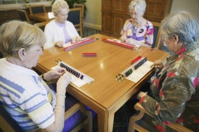 group of four people playing Mahjong