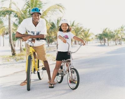 A dad and his daughter ride bikes together along the beach.
