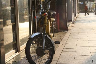 A moped is parked on a sidewalk outside of a cafe.