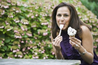 A woman eats an icecream cone on an outdoor bench.