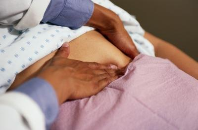 Doctor examining abdomen of patient