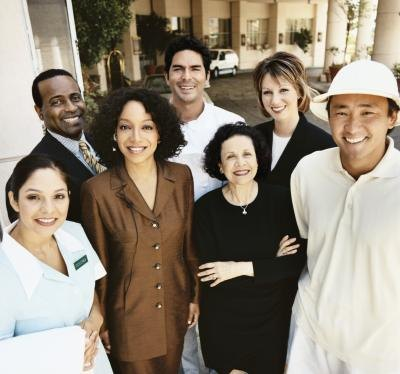 Portrait of a hotel staff standing in front of the hotel.
