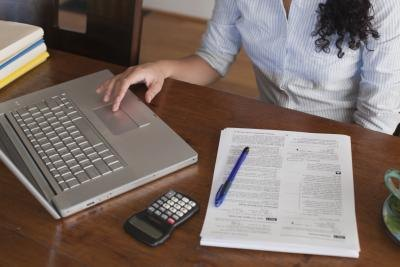 A woman fils out tax documents at a desk.