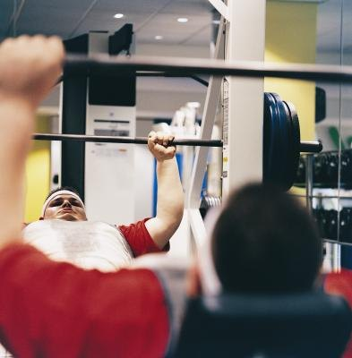 An overweight endomorphic man lifts weight at the gym.