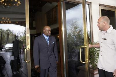 A hotel employee opens the door for a smiling guest.