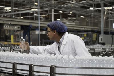 An employee in a bottled water plant inspects the products.