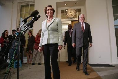 Speaker of the House, Pelosi, approaches microphones.