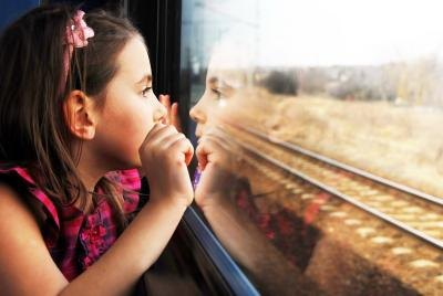 Young girl looking out train window.